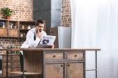 hezký samotář podnikatel, čtení novin v kuchyni