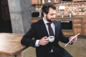 boční pohled hezký samotář podnikatel při pohledu na tabletu a drží šálek kávy v kuchyni