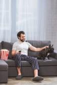 Fotografia bel solitario palming bulldog e che tiene il telecomando sul divano nel soggiorno