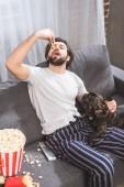 vysoký úhel pohled hezký samotář a jíst hranolky na pohovce v obývacím pokoji s buldok