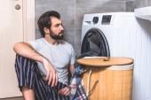szép magányos ülő földre, és nézi a fürdőszobában mosógép