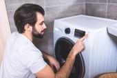 schöner Einzelgänger, der Waschmaschinenprogramm im Badezimmer einstellt