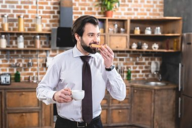 handsome loner businessman eating toasts on breakfast at kitchen
