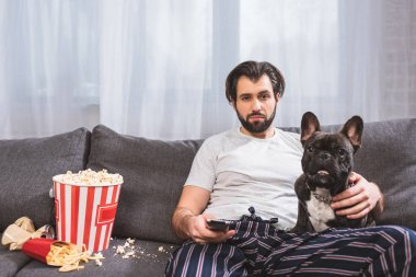 handsome loner watching tv with bulldog on sofa in living room
