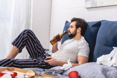 male loner playing video game in bedroom and drinking beer