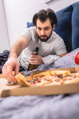handsome loner taking piece of pizza and holding bottle of beer on bed in bedroom