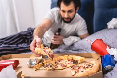 handsome loner taking piece of pizza on bed in bedroom