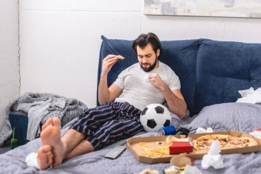 handsome loner eating pizza on bed in bedroom