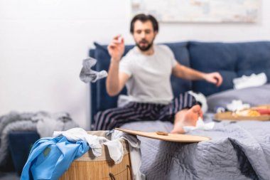 loner throwing dirty sock into basket with laundry in bedroom