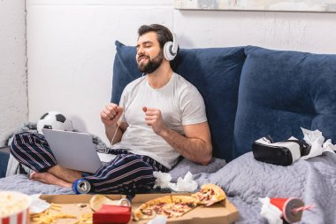 happy handsome loner listening music with laptop in bedroom