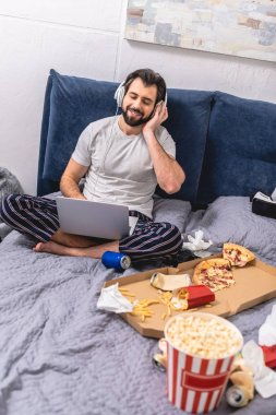 handsome loner listening music with laptop in bedroom