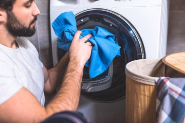 side view of loner putting laundry in washing machine in bathroom
