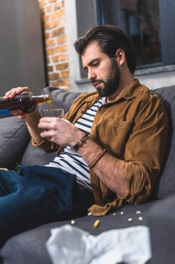 loner pouring whiskey in glass at living room