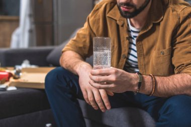cropped image of loner with hangover holding glass of water at living room