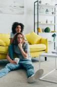mladý muž s prstem na ústech sledování televize s africká americká přítelkyně