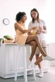 mladá africká americká žena cinkání vínem brýle s přítelem v kuchyni