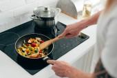 Fotografie oříznutý snímek člověka vaření zeleniny na pánvi na elektrický sporák