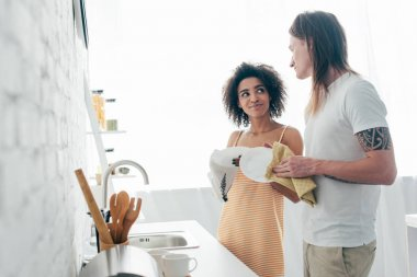 multicultural young couple washing dishes and looking at each other