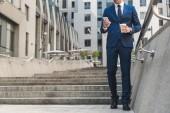 oříznuté záběr podnikatel v stylovém obleku s kávou jít pomocí smartphone zatímco jít dolů po schodech