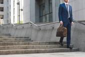 Oříznout záběr podnikatel v stylovém obleku s Aktovkou jít dolů po schodech