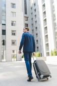 Fotografie handsome young businessman with luggage walking by business district