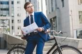 Fényképek fiatal üzletember elegáns ruha újság támaszkodva kerékpár