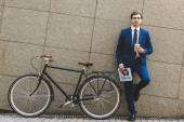 handsome young businessman in stylish suit with newspaper and bicycle leaning on wall