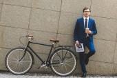 Fényképek csinos fiatal üzletember, elegáns ruha, újság és a kerékpár, támaszkodva a fal