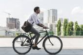 boční pohled na mladíka v stylové oblečení, jízda historických kol na město ulice