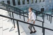 pohledný mladý muž, chůzi po schodech s notebookem na městské ulici