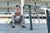 Fotografie Spodní pohled na pohledný mladý muž s papíru šálek kávy čtení knihy na schodech na ulici