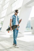 Photo stylish young man with skateboard using smartphone on street of modern city