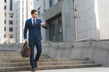 attractive young businessman in stylish suit with briefcase looking at watch in business district