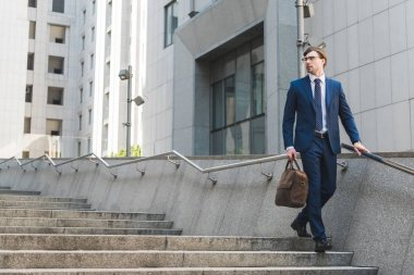 attractive young businessman in stylish suit with briefcase in business district