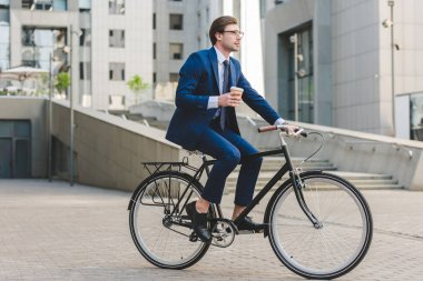 young businessman in stylish suit with coffee to go sitting on vintage bicycle