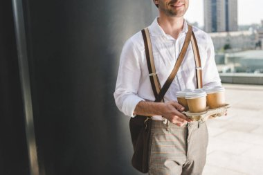 cropped shot of stylish man with paper coffee cups on cardboard tray