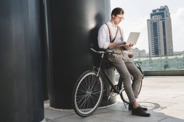 stylish young man working with laptop while leaning on vintage bicycle