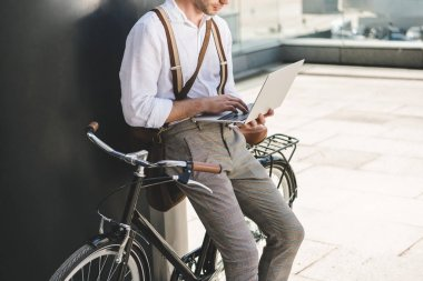 Cropped shot of man working with laptop while leaning on vintage bicycle stock vector