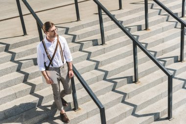 high angle view of attractive young man with folded laptop walking on stairs on city street