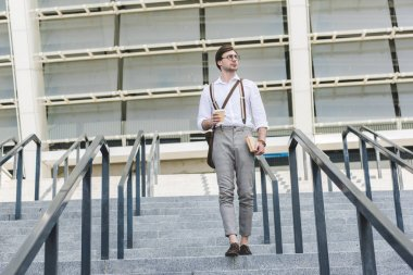 attractive young man walking down stairs in front of stadium with book and coffee to go