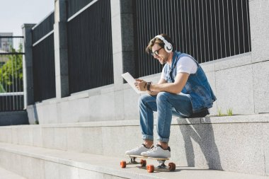 stylish young man with skateboard listening music with headphones and tablet on street