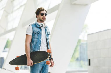 stylish young skater in denim clothes with longboard and headphones