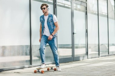 handsome young skater in denim clothes riding skateboard
