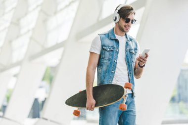 handsome young man with longboard using smartphone on street of modern city