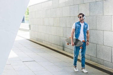 smiling young man in headphones with skateboard walking by street