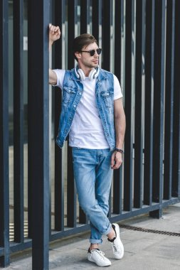handsome young man in denim vest leaning on fence on city street