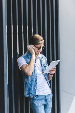 stylish young man listening music with tablet and headphones