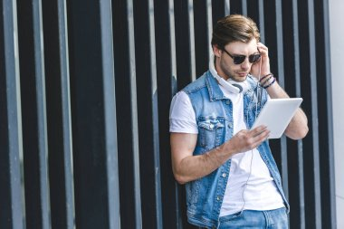 handsome young man listening music with tablet and headphones