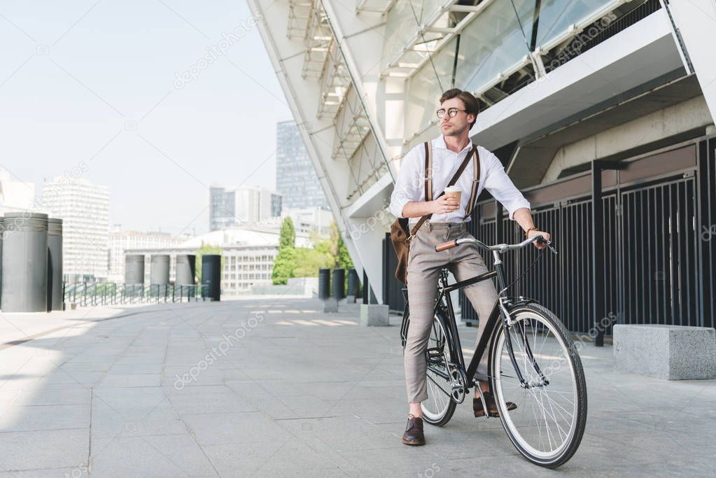handsome young man with paper cup of coffee on vintage bicycle near sports stadium building