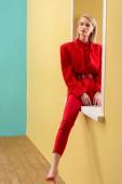 Fényképek elegáns piros színű dekoratív ablakban ül a gyönyörű töprengő nő